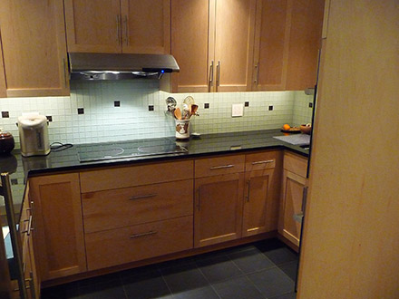 After - New countertops, cabinetry, appliances, lighting, glass tile backsplash, and floor tile.