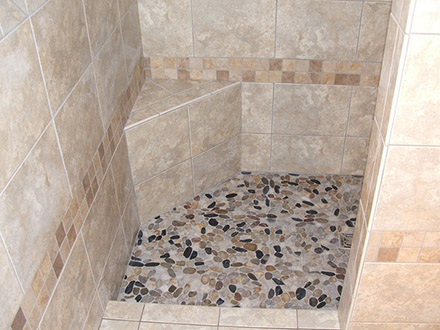 Walk in shower with bench seat. Natural stone on floor with ceramic till on walls.