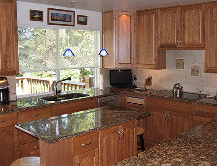 After - New cabinets, countertops, tile backsplash, lighting, fixtures, flooring, and appliances.
