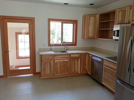 New kitchen included flooring, cabinet installation, countertops, fixtures, windows, and hardwood staircase.